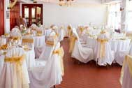 Wedding reception with white covered chairs decorated with gold sash bows