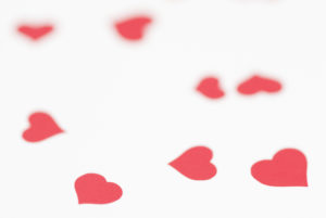 Multi soft red hearts scattered on a white background