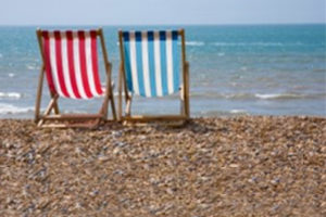 Striped Striped deckchairs on a pebble beach by the sea