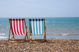 Deckchairs on a pebble beach by the sea