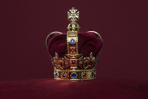 English Royal Crown on a velvet cushion on a deep red background