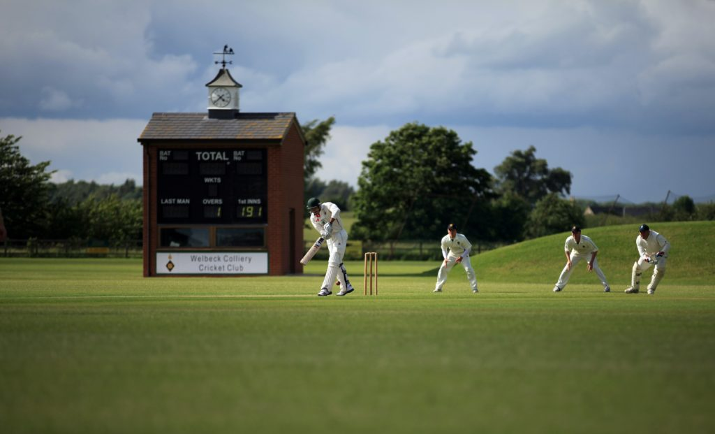 4 cricket players in white on a cricket green